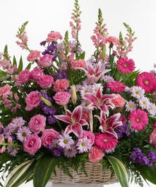 olorful mix of pink and lavender flowers including roses and lilies artfully designed in a basket.  Approximate size for the standard design is 32
