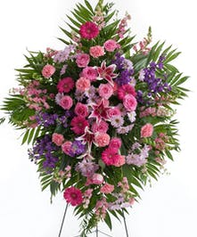 Mix of pink and lavender flowers displayed on an easel stand. Roses, lilies, daisy's and other assorted flowers. Approximate size of  the standard design is 28