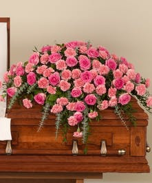 Delicate mix of pink roses and pink carnations with lush greens designed for the casket.