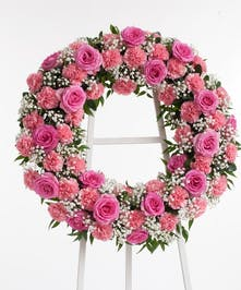Wreath display featuring stunning pink roses and pink carnations.Approximate size of the standard design is 18