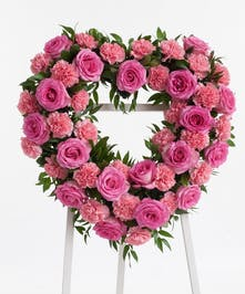 Stunning open heart easel display featuring complementing pink roses and carnations. Approximate size of the standard design is 18