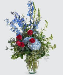 Patriotic floral design featuring seasonal flowers including roses, hydrangea, and delphinium in a clear glass vase. Approximate size of standard design is 16