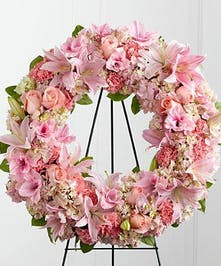 A soft yet sunning wreath display done in shades of pink featuring roses, lilies, and other accenting flowers. Approximate size of the standard design is 18