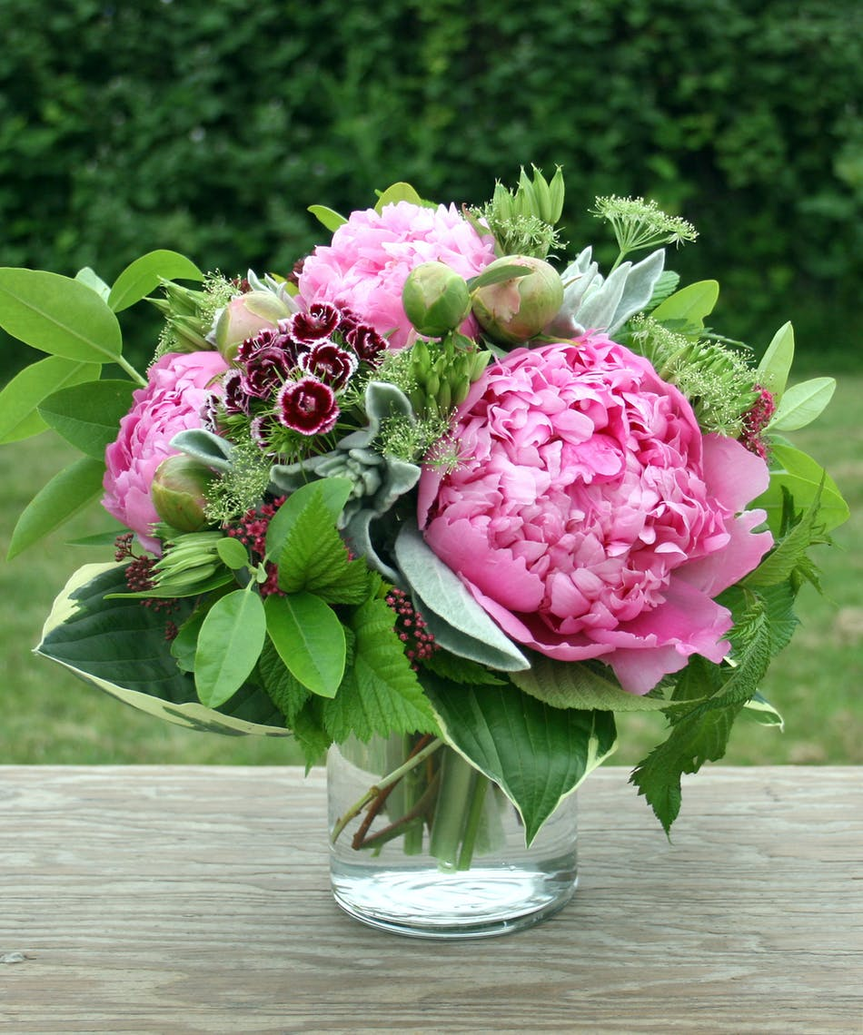 Fresh cut peonies with garden flowers and unique herbs.
