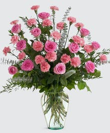 Mix of pink roses and carnations artfully designed in a clear glass vase.  Approximate size of standard design is 16