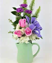 This stunning arrangement is sure to leave her breathless! Pink and Lavender Purple ribbon accent the Clear Glass keep sake Beverage Pitcher.