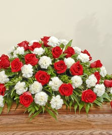 Red roses and white carnations beautifully arranged with lush greenery for the casket in this classic flower combination.