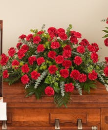Classic red carnations and lush tropical greens are used to create this traditional casket spray.