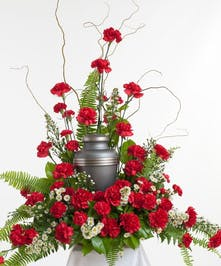 Classic red carnations and other accenting greens create a time honored tribute for a loved one. This arrangement is specifically designed with room for a memorial urn.