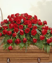 Red roses with lush greens are artfully designed to make a statement in this casket spray.