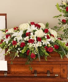 Classic casket designed with a mix or premium red and white flowers including hydrangea, roses, and lilies.
