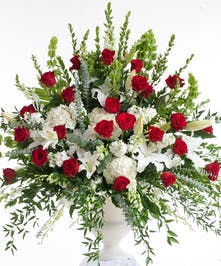 Stunning mix of red roses and white lilies designed in a white container. Approximate size for the standard design is 20