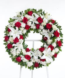 Classic wreath designed with a mix or red roses, white lilies, and other accenting flowers displayed on an easel. Approximate size of the standard design is 18