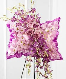 A pillow shaped display full of soft and richly colored pink flowers, including chrysanthemums, roses, and orchids.