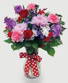 This mix of red roses, mums, carnations, stock, and assorted fillers is accented by a sparkling red heart.  A perfect gift for your Valentine!