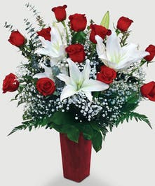 A dozen roses are complimented by the beauty and sweet scent of fragrant white lilies.