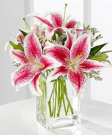 Fragrant pink Stargazer lilies are accented with pink statice and arranged in a clear glass vase.