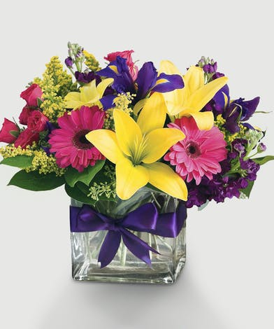 Bright colors fill this cube vase with everything we love. Lilies, Roses and Iris are the ideal selection for someone special.