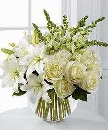 White roses, Asiatic lilies, snapdragons and carnations mix with fresh greens give this unique and beautiful arrangement an elegant feel.