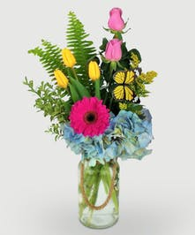 fun mix of spring flowers in a clear glass vase with natural rope handle accent.  Fresh tulips, daisy and roses designed in a bright mix of yellow, blue, pinks.