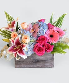 A handmade wooded Box overflowing with bright-colored roses, hydrangea and gerbera daisies