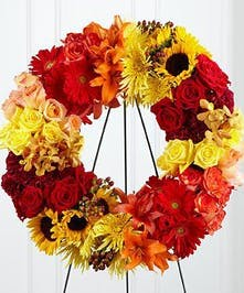 Modern wreath display featuring clusters of yellow sunflowers, red roses, orange lilies and other accenting flowers. Approximate size of the standard design is 18