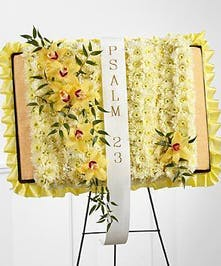 Floral representation of the Holy Bible made with chrysanthemums and featuring delicate trail of orchids down one page.