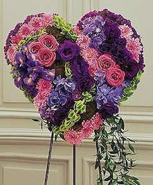Roses, carnations and other accenting flowers in shades of purple and green adorn this stunning solid floral heart. Approximate size of the standard design is 18