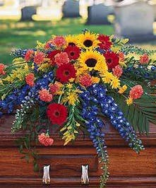 Mix of bright summer flowers in primary colors featuring sunflowers, delphinium, carnations, and other garden inspired accents.
