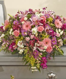 Traditional mix of lilies, gerbera daisies, carnations and other flowers in pinks and purples with yellow and white accents.