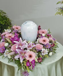 Traditional mix of lilies, carnations, and daises in shades of pink, white, and lavender create peaceful design for an urn placement.