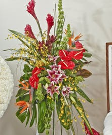 Tropical easel spray featuring lilies, orchids, Ginger and other tropical accents. Approximate size of the standard design is 28
