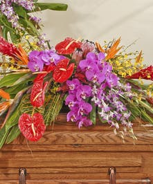 Tropical casket spray featuring exotic orchids, Anthurium,birds of paradise and other tropical flowers surrounded by lush tropical greens.