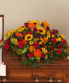 A casket designed in a Tuscany-inspired palette that is filled with brilliant sunflowers, roses, and other accent flowers.