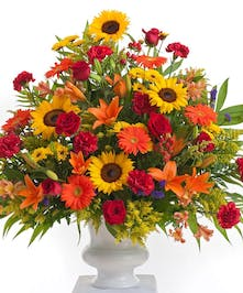 A bright mix of orange, red, and yellow flowers including , roses, carnations, and sunflowers designed in a white container. Approximate size is 24