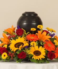 Tuscan Mix of roses, sunflowers, lilies, and other accenting flowers. Creating a vibrant and beautiful place for a memorial urn. Memorial Urn not included.
