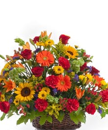 Mix of red roses, sunflowers, and carnations artfully designed in a basket. Approximate size for the standard design is 22