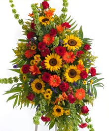 Stunning mix of sunflowers, lilies, roses, and other accent flowers in our popular Tuscan mix displayed on an easel. Approximate size of  the standard design is 28