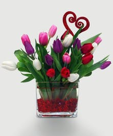 A mix of pink, white, purple, and red tulips in a rectangle vase with gems at the bottom.