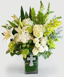 This beautiful design Features Our leaf wrapped signature clear vase. Lilies, roses, Hydrangea amongst other Elegant greenery