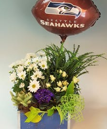 A blue wooden box filled with tropical green and blooming plants to celebrate the Seahawks! Includes an official NHL Seahawks mylar balloon.