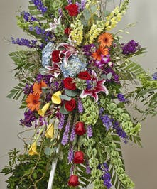 Vivid and bright easel display featuring lilies, hydrangea, gerbera daisies, and roses. Approximate size of the standard design is 28