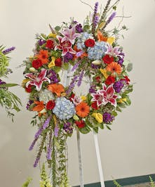 Brightly colored wreath displayed on an easel featuring red roses, lilies, hydrangea and other accent flowers. Approximate size of the standard design is 28