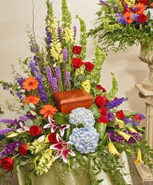 This Vivid mix of roses, hydrangea, lilies, and other complementary flowers provide a bold and peaceful place for a memorial urn.