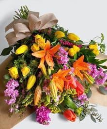 This vibrant mix of the freshest seasonal flowers wrapped in paper with a burlap bow.