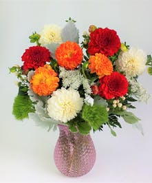 Fresh Garden Dahlias combined with elegant garden textures and blossoms. Assorted Colors of Dahlias designed in a Clear Dimple textured Glass  Vase, .