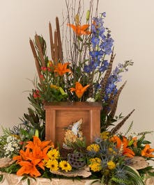 This design features lilies, delphinium, and other accenting flowers. This arrangement has a nice space created specifically for an urn placement at a memorial service.