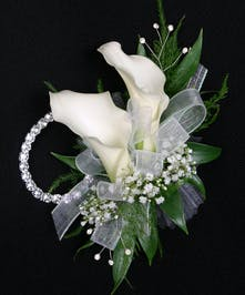 Two elegant and contemporary calla lilies create this beautiful wristlet and is accompanied by a coordinating boutonniere.
