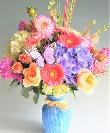 The Best  flowers and the Best Beaches! Send hydrangea, roses and Gerbera Daisy with this mix of our freshest flowers in a Clearvase wrapped with natural raffia.