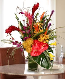 Bright mix of exotic Ginger, birds of paradise and orchids in a vase